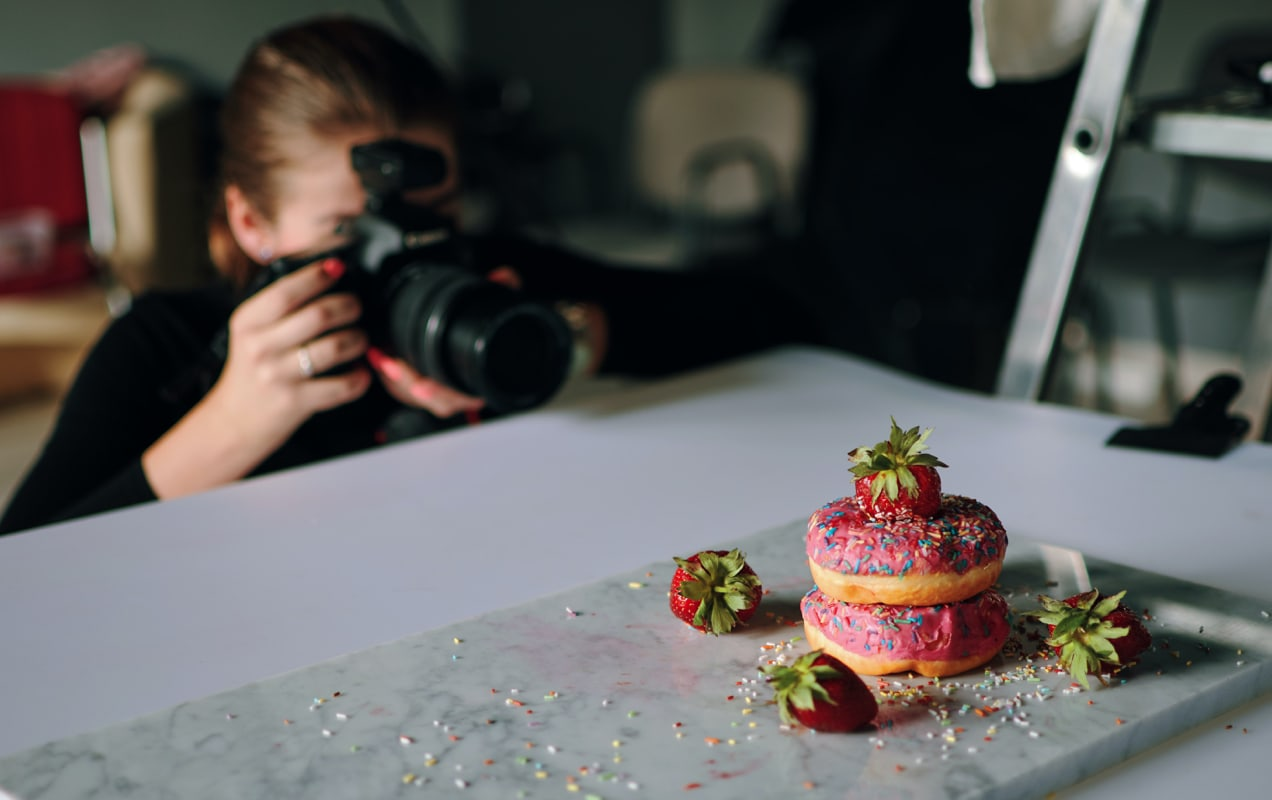entrepreneur taking pictures of donuts with a DSLR camera